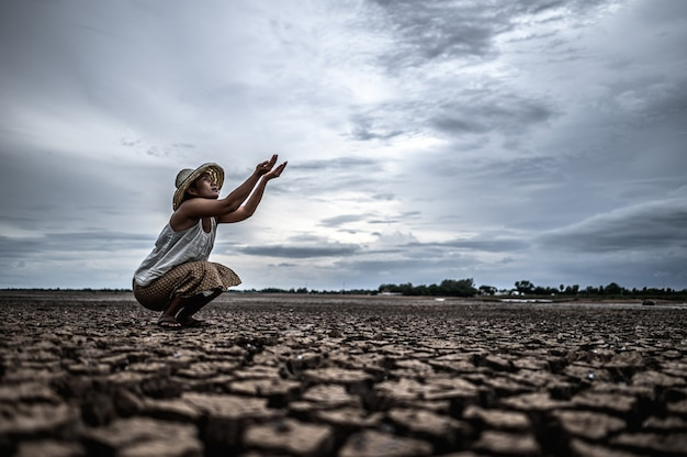 A woman is sitting asking for rain in the dry season, global warming