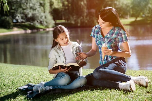 Женщина сидит рядом с ребенком и указывает на книгу. также она держит один кон мороженого. они вместе смотрят на открытую книгу.
