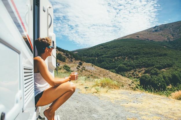 Woman is sitting on a caravan step