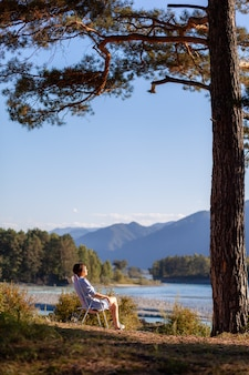 A woman is sitting on a folding chair on the bank of a mountain river on a nice, warm day under a large tree. a calm and quiet place to relax and reflect. equipment and a tourist's rest.