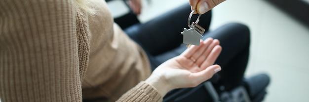 여자는 휠체어에 앉아 있고 열쇠는 그녀에게 전달됩니다. 장애인을위한 주택 확보 개념