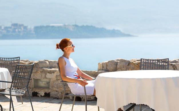 山の景色を望むモンテネグロの高級ホテルの海の見えるテラスに座っている女性