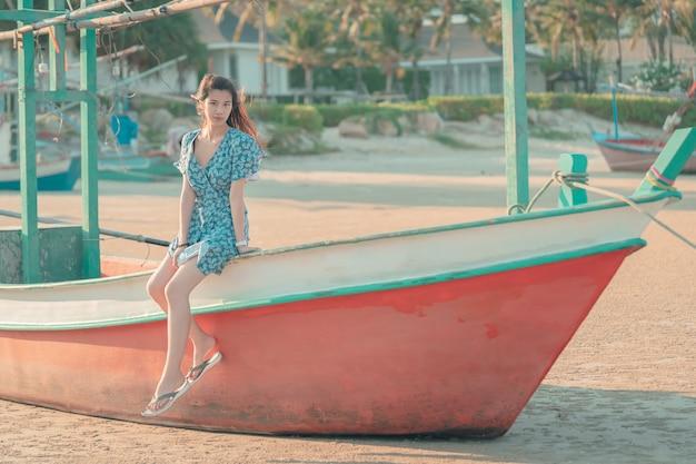 女性はリラックスしたビーチボートに座っています。