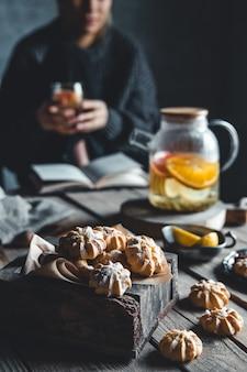 여자는 나무 태블릿에 신선한 자 몽의 조각과 뜨거운 차 한 잔 위에 앉아있다. 건강 음료, 에코, 비건.