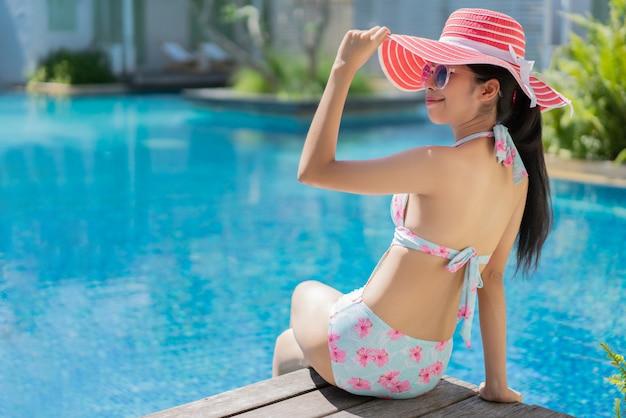 Woman is sitting she wears a bikini relaxing in the summer