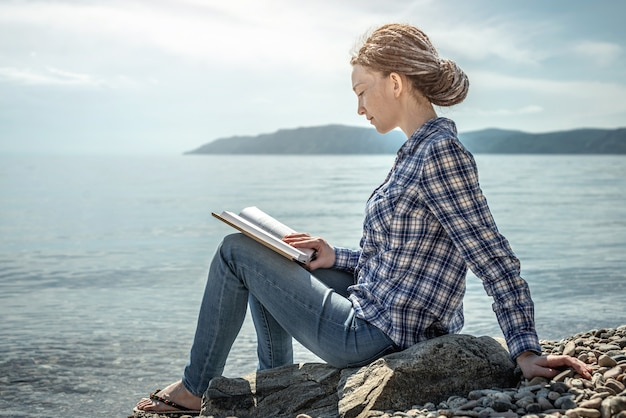 Woman is sitting on the stony coast of a large pond reading and enjoying the solitude and nature