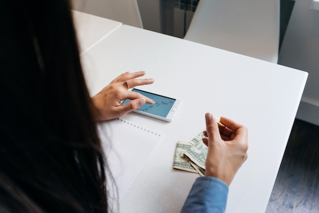 Woman is sitting at the table and is looking at the graph on the background of money on the table
