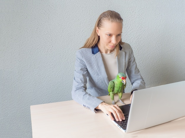 Woman is sitting with a green parrot at the computer. remote work