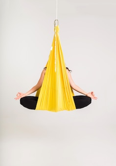 A woman is sitting in a yellow hammock in the padmasana pose on a white wall