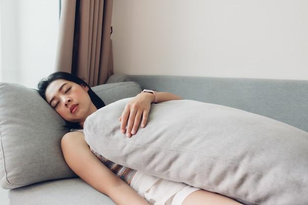 Женщина спит на диване, чувствуя себя расслабленным в усталый день.