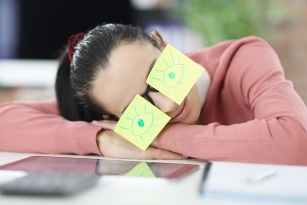 Woman is sleeping at workplace. glasses having stickers with painted eyes. rest at work concept