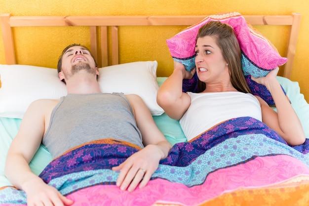 여자는 침대에서 코골이 남편 때문에 잠 못 이루고 화가납니다.