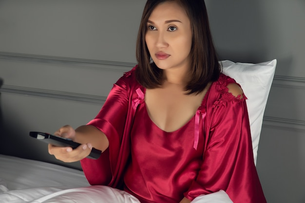 Woman is sleepy while she is watching television in the bedroom at night