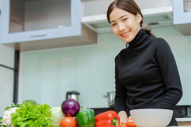 女性は料理を準備するために野菜をスライスしています