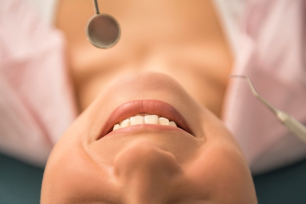 A woman is smiling while being at the dentist.