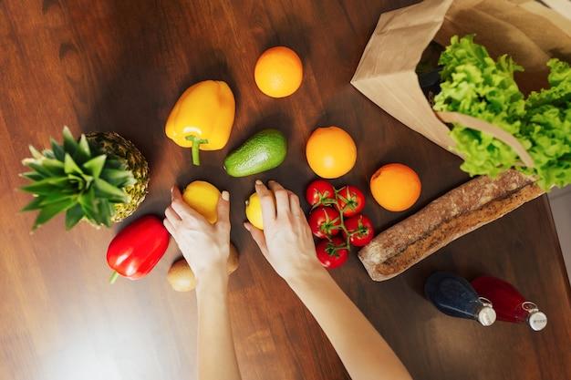 女性がキッチンで購入した後、食品を分類しています