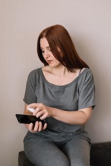 女性はアルコール、消毒剤スプレーを携帯電話にスプレーし、covid-19ウイルスの感染を防ぎ、細菌や細菌の汚染、ワイプまたはクリーニング電話