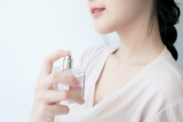 Woman is spraying perfume at the neck.