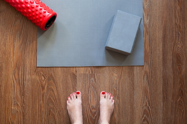Woman is standing barefoot on floor in front of gymnastic mat and roller