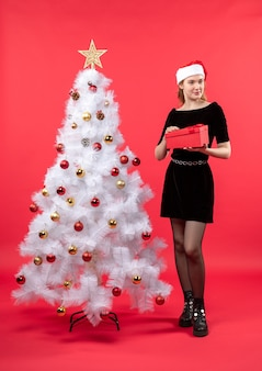 A woman is standing next to the christmas tree