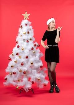 Una donna è in piedi accanto all'albero di natale