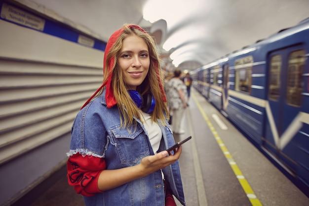 여자는 도착 기차 근처 지하철 역에 서 있습니다.