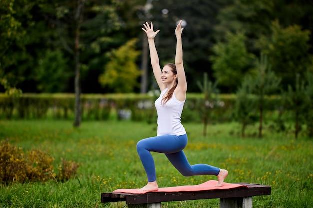 Женщина стоит в позе йоги в общественном парке на скамейке