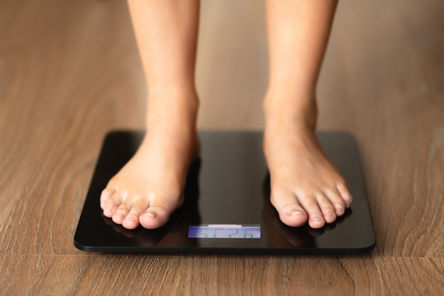 A woman is standing on the scales on a wooden floor