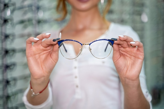 여자는 안경점에서 많은 안경을 배경으로 서 있다. 안경을 쓰고 서십시오. 시력 교정. 여자는 안경을 손에 들고 있습니다. 확대.