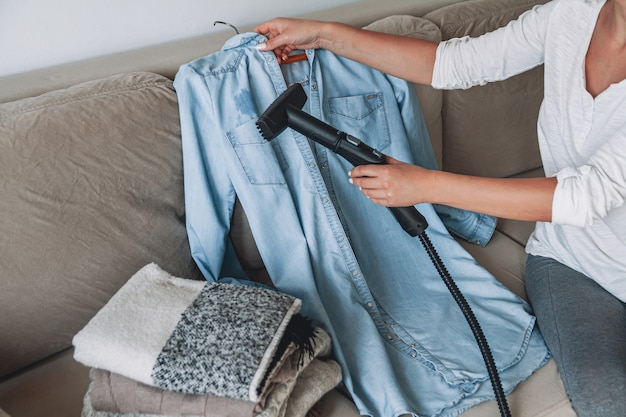 Woman is steaming steam cleaner shirt in a room