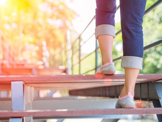 Woman is stepping up a staircase with lens flare or sunspot