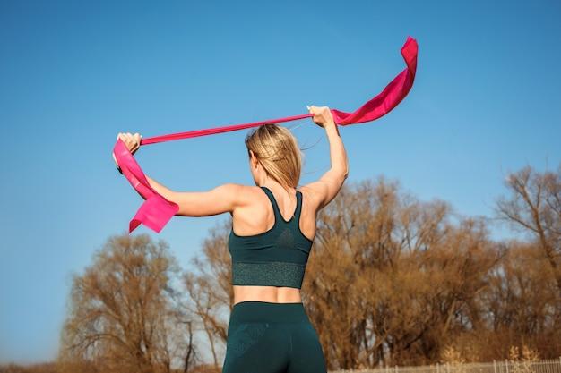 Женщина протягивает руки с резинкой, вид сзади, тренируясь на свежем воздухе весной