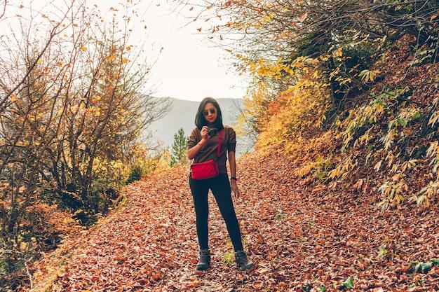 Женщина принимает фото ландшафта природы пока пеший туризм на холме в осени.