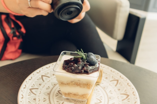 Woman is taking a photo of her blueberry cheesecake.