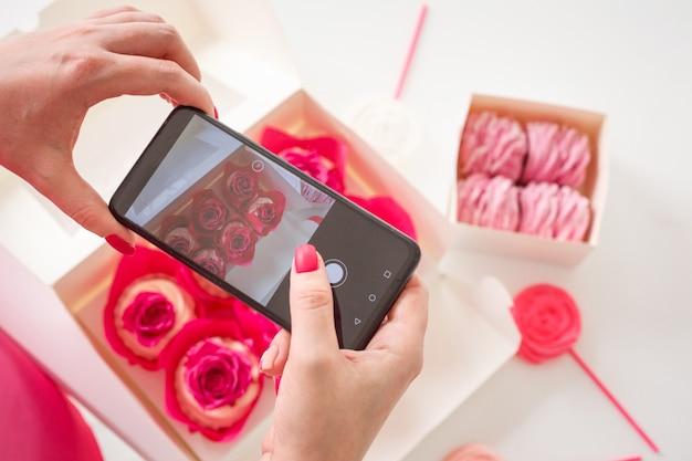 여자가 스마트폰으로 집에서 만든 과자 컵케이크와 마시멜로 사진을 찍고 있다