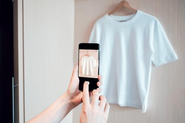 Женщина фотографирует на смартфоне использованную одежду для перепродажи или благотворительности