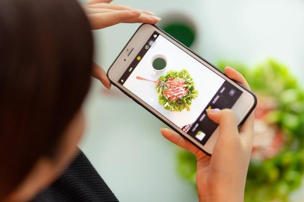 女性は食事の写真を撮っています