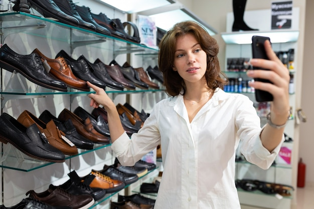 Woman is taking selfie with boots for men in shop and pointing at black shoe