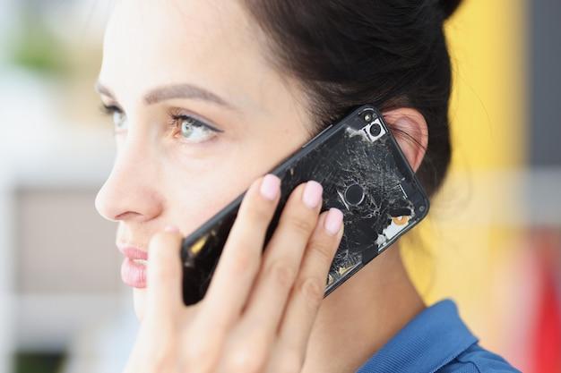 Woman is talking on broken black smartphone mobile equipment repair service concept