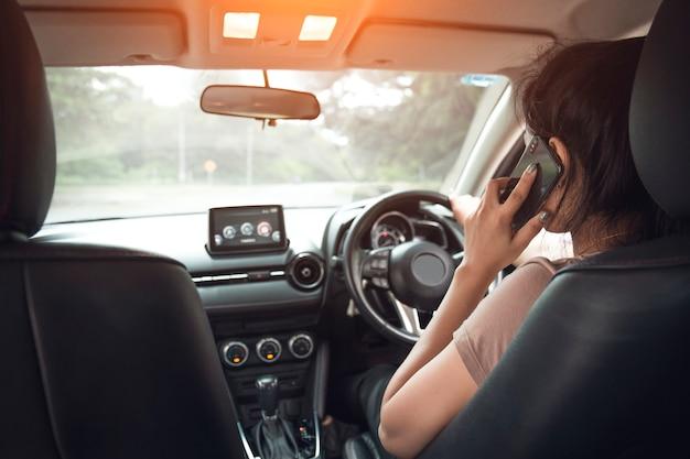 여자는 차를 운전하는 동안 그녀의 전화 통화