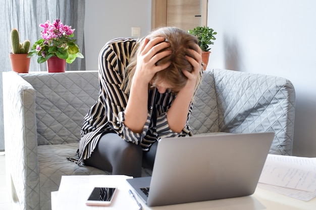Woman is thinking about working with a laptop at table. difficulties problems at work