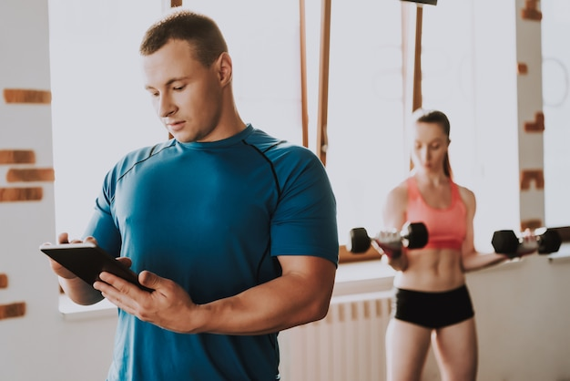 Woman is training in big gym with trainer