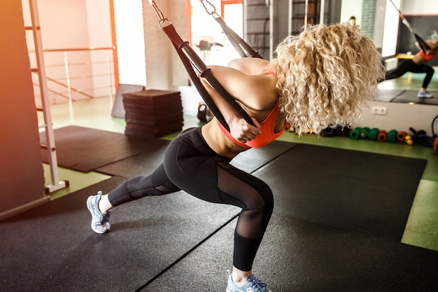 A woman is training with a rubber bands, she is leaning forward.