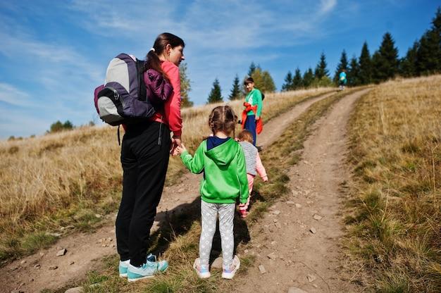 女性は子供と一緒に旅行しています。山の中のお母さん。子供たちと一緒に山の頂上に登ります。バックパックを上に登った。
