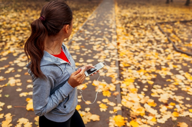 Woman is turning the music on before running in autumn park. healthy lifestyle