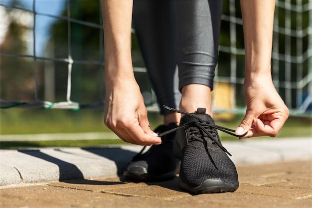 女性はサッカーゲートの近くの夏のスニーカーを結ぶ