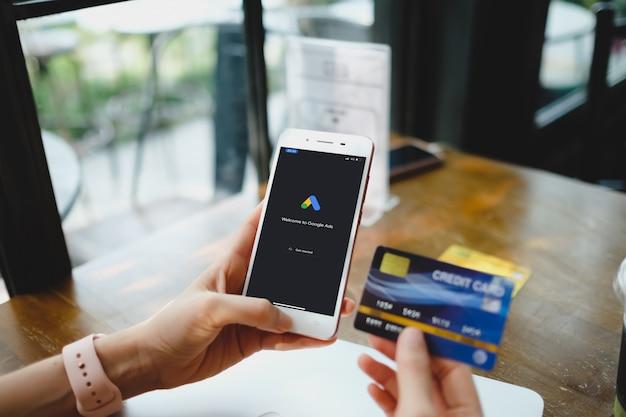 Женщина печатает на google ads и кредитной карте с мобильного телефона.