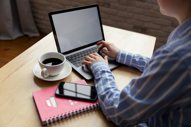 女性は自宅でノートパソコンのキーボードをフリーランスで入力し、電子メールをチェックし、オンラインショッピングのための情報を入手しています。高品質の写真