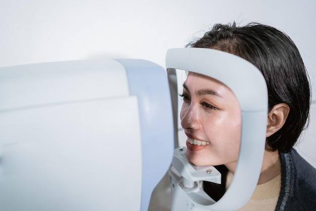 A woman is undergoing an examination using an eye examiner computer in an eye clinic room