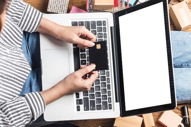 女性はコンピューターを使ってオンラインで買い物をしています